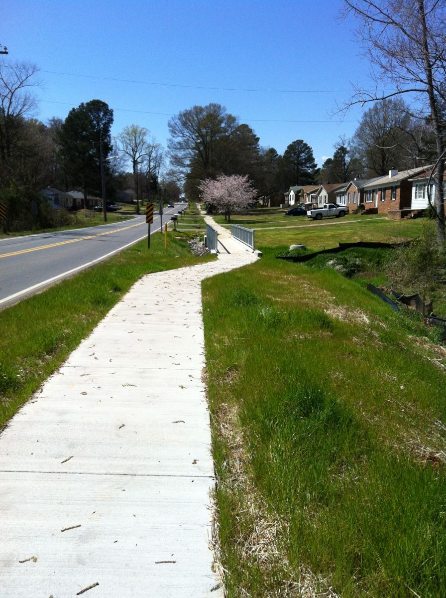 Image of neighborhood sidewalk, with grassy edges, and houses on 1 side